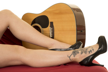 woman legs with tattoo on foot in front of guitar