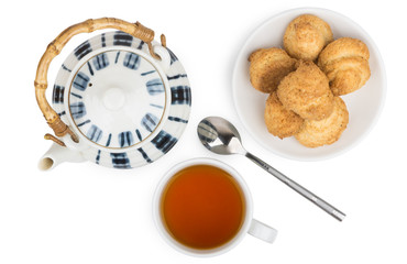 Porcelain teapot, cup of tea and biscuits on  saucer