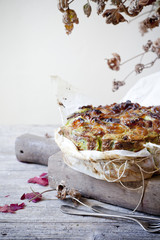 onions savoury cake on wooden cutting board with autumnal leaves