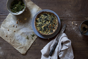 baked green wild asparagus quiche on wooden table