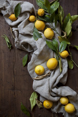group of fresh lemons with leaves on wooden table with cloth