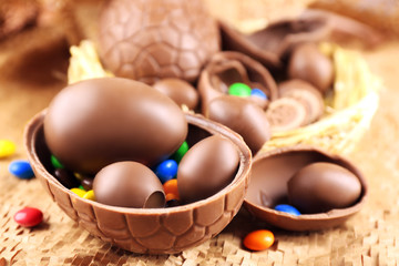 Chocolate Easter eggs on wicker fabric in nest, closeup