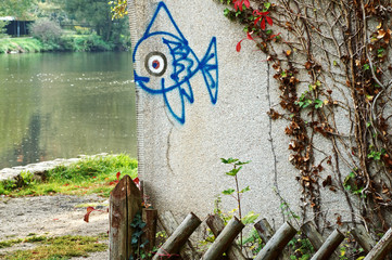 Graffiti blue fish on the edge of the wall on the river bank.