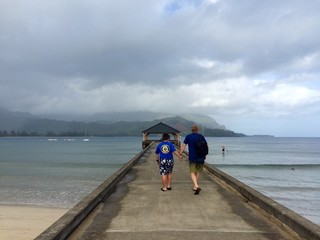 Father and son walk along Hanalei Pier in Kauai