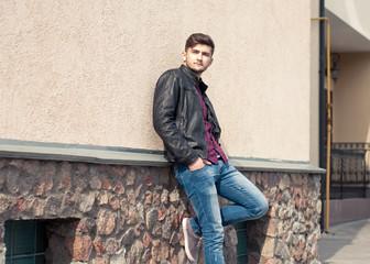 Fashionable handsome man model posing outdoors. Street fashion