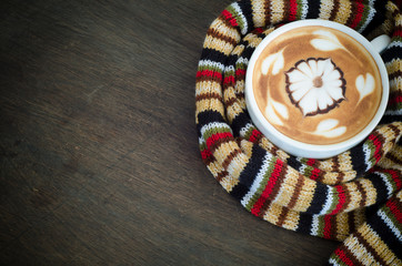 Cup of coffee surrounded the warm scarf on wooden background