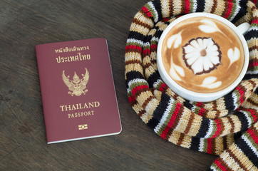 Cup of coffee surrounded the warm scarf  and Thai passport