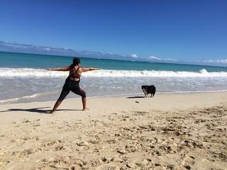 Woman doing yoga in the beach