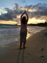 A woman does a sun salutation at sunrise on Kailua Beach Oahu