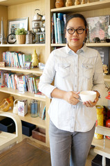Asian woman standing and holding coffee cup with bookshelves bac