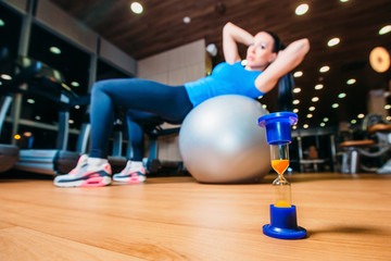 girl working out at gym with a ball,  in the foreground of an