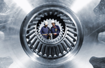 Wall Mural - industry workers seen through a giaant gear shaft