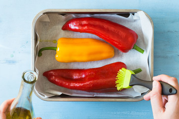 Colorful Red and Yellow Peppers Being Brushed with Olive Oil