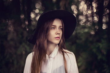portrait of a beautiful girl in a hat in the spring