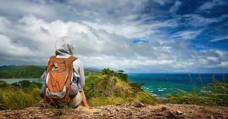 Woman backpacker admiring a beautiful seashore landscape Wall mural