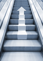 Shining metal escalator with white arrow moving up