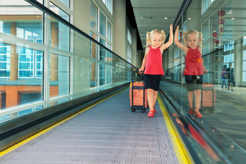 Joyful girl with her trunk on airport moving walkway