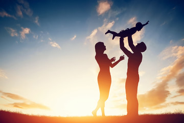 Fototapeta Happy family together, parents with their little baby at sunset obraz