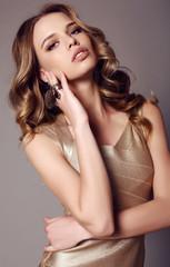 beautiful sensual woman with dark hair in elegant gold dress