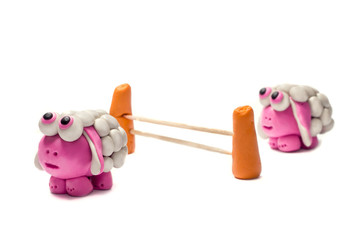 Little plasticine sheep jumping over a fence.
