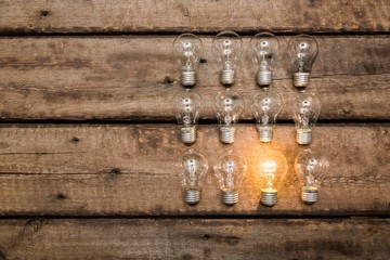 Background. Glowing bulb uniqueness concept on brown wooden