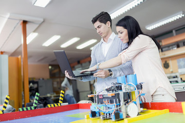 Two smart students programming a robot