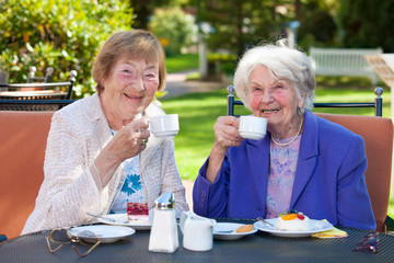 Elderly Best Friends with Coffee at Outdoor Table.