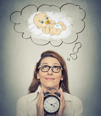woman anticipating a baby looking up holding alarm clock