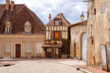 Fototapete - Quaint street in a town in Burgundy, France with timbered house