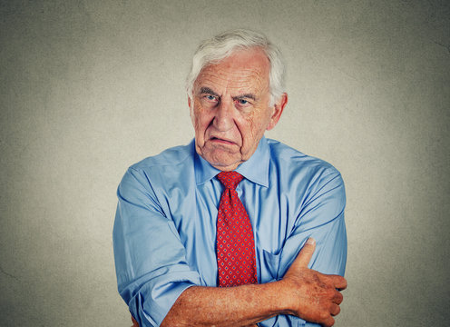 Angry grumpy pissed off senior mature man gray background