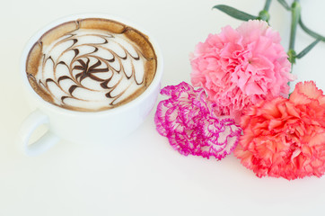 a cup of latte art and carnation on white background