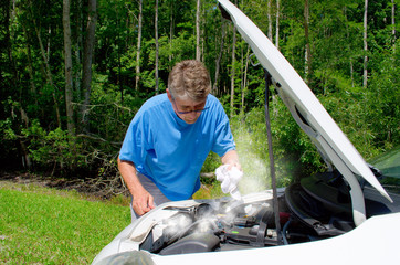Man in trouble working on overheated smoking broken down car