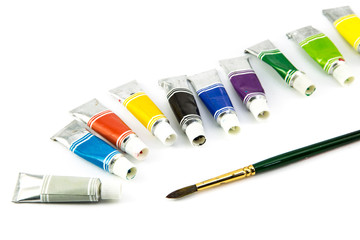 Tubes of  colored paint and brush on white background