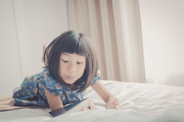Vintage tone of Young Girl Lying On Her Bed and Reading A Book w