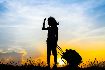 Silhouette Girl with a suitcase with sun set.