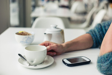 Woman using phone and having tea
