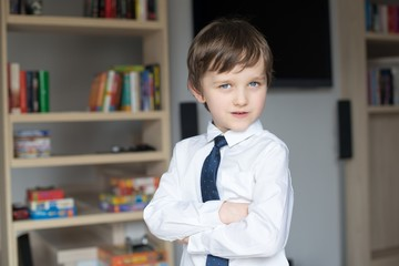 Elegantly dressed in a white shirt and tie little boy