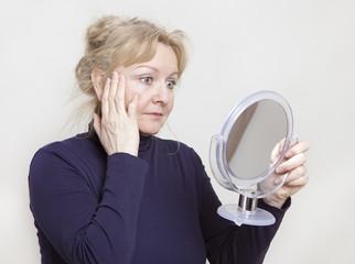 Seniorin schaut in Spiegel