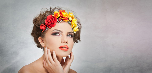Portrait of beautiful girl in studio with yellow and red roses