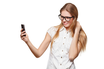 Happy young girl taking selfie with cell phone, in glasses