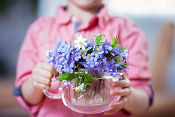 Little hands, holding glass vase with forest spring flower bouqu