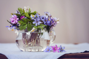 Glass vase with fresh spring forest flowers