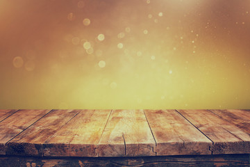 rustic wood table in front of glitter green and gold bright bok