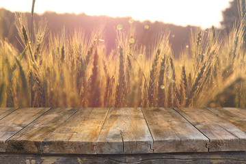 wood board table in front of field of wheat on sunset light. Rea