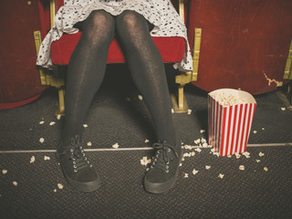 Woman in theater with popcorn on floor