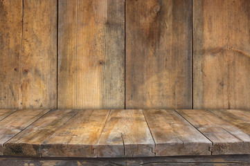 Grunge vintage wooden board table in front of old wooden backgro