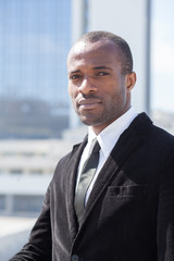 black businessman portrait on skyscrapers background