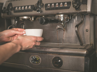 Hands placing cup under coffee machine
