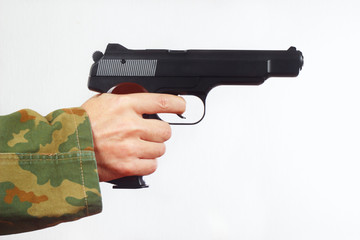 Hand in camouflage uniform with a semi-automatic gun