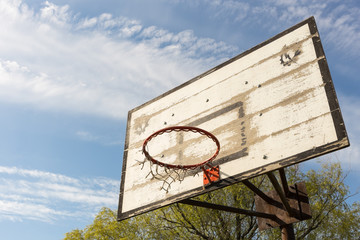 Outdoor old basketball hoop with blue sky and clouds